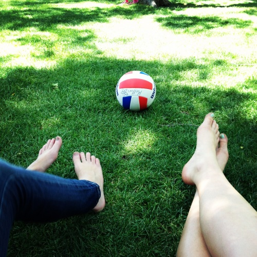 A volley ball sits in the grass, two pairs of legs are stretched out in front of it