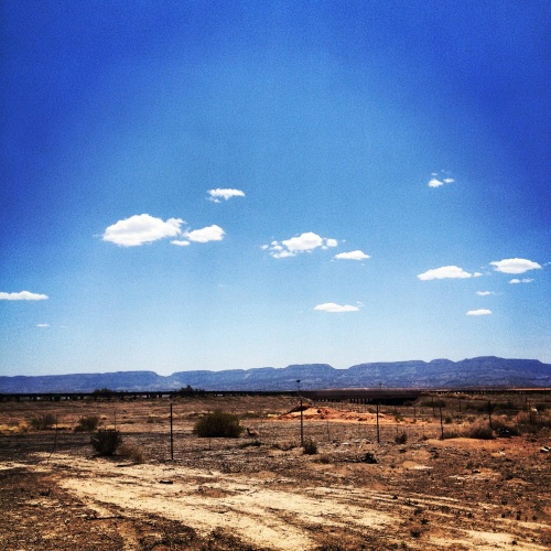 a blue sky and a barren landscape