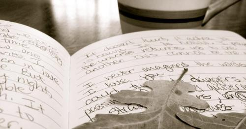 a notebook full of words lies open on a table next to a coffee cup